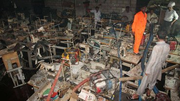 Arbeiter untersuchen am 13. September 2012 die Textilfabrik Ali Enterprises in Karachi, in der am 11. September 2012 mehr als 250 Menschen verbrannten